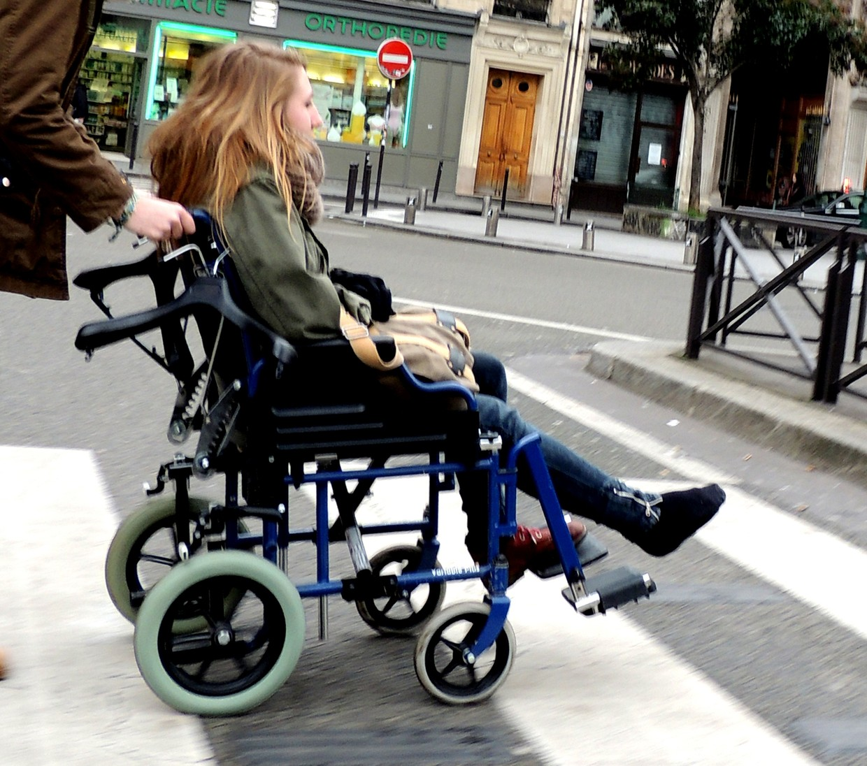 Beautiful girl in a wheelchair with her right leg in a cast covered by a sock.