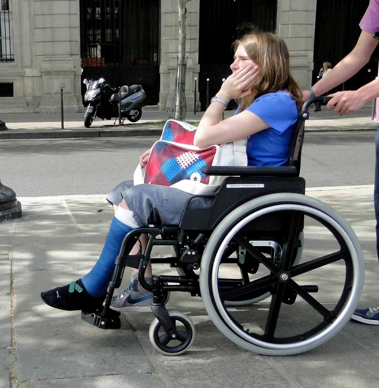 Woman with blue short legcast in wheelchair