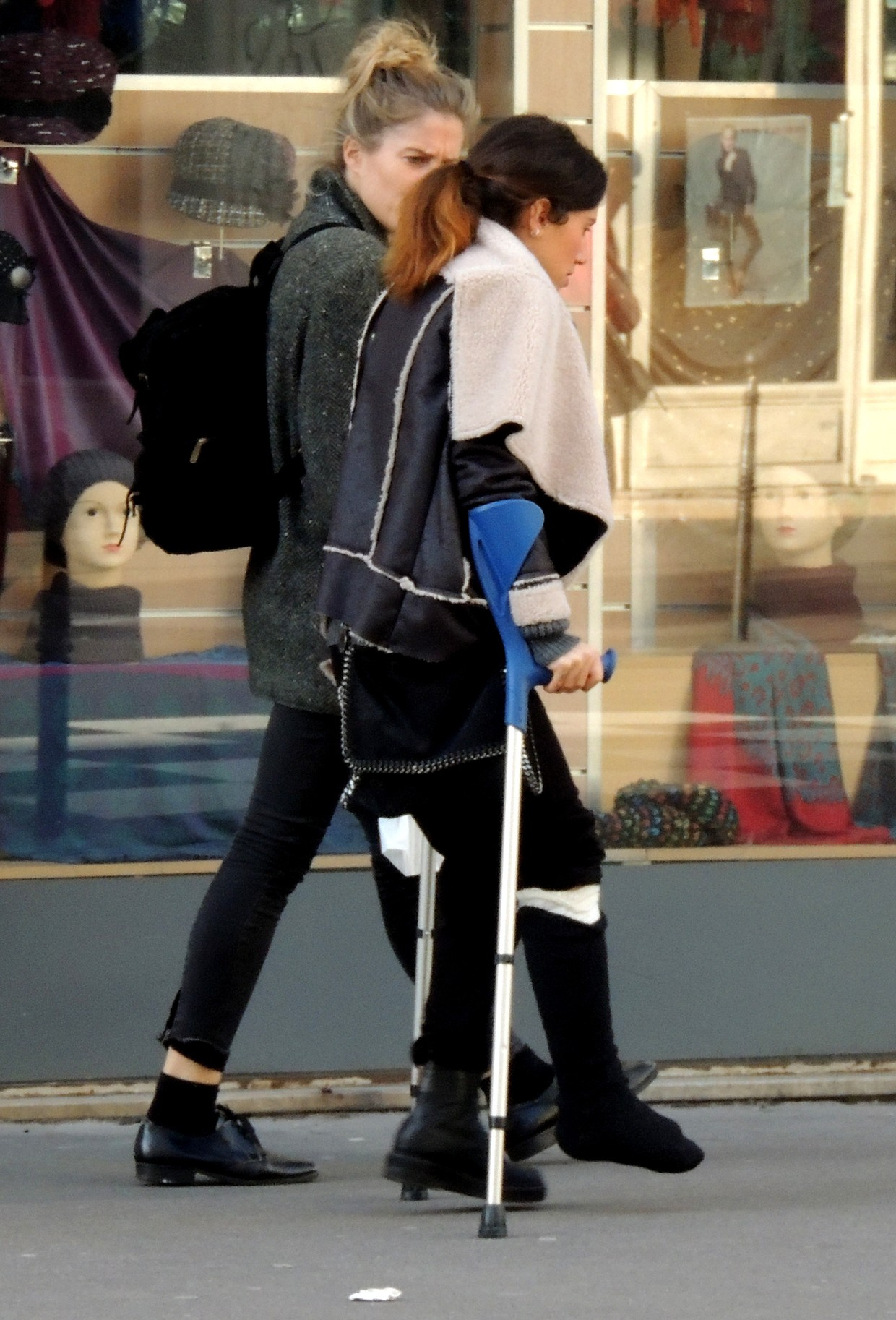 Woman with black sock over white plastercast on crutches