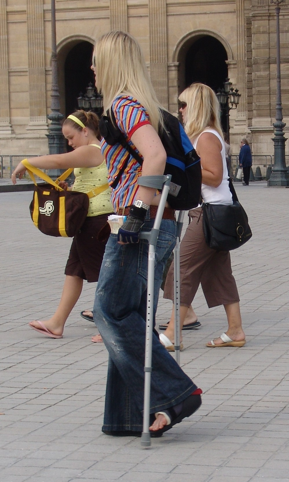 Blonde woman in black SLC on crutches.