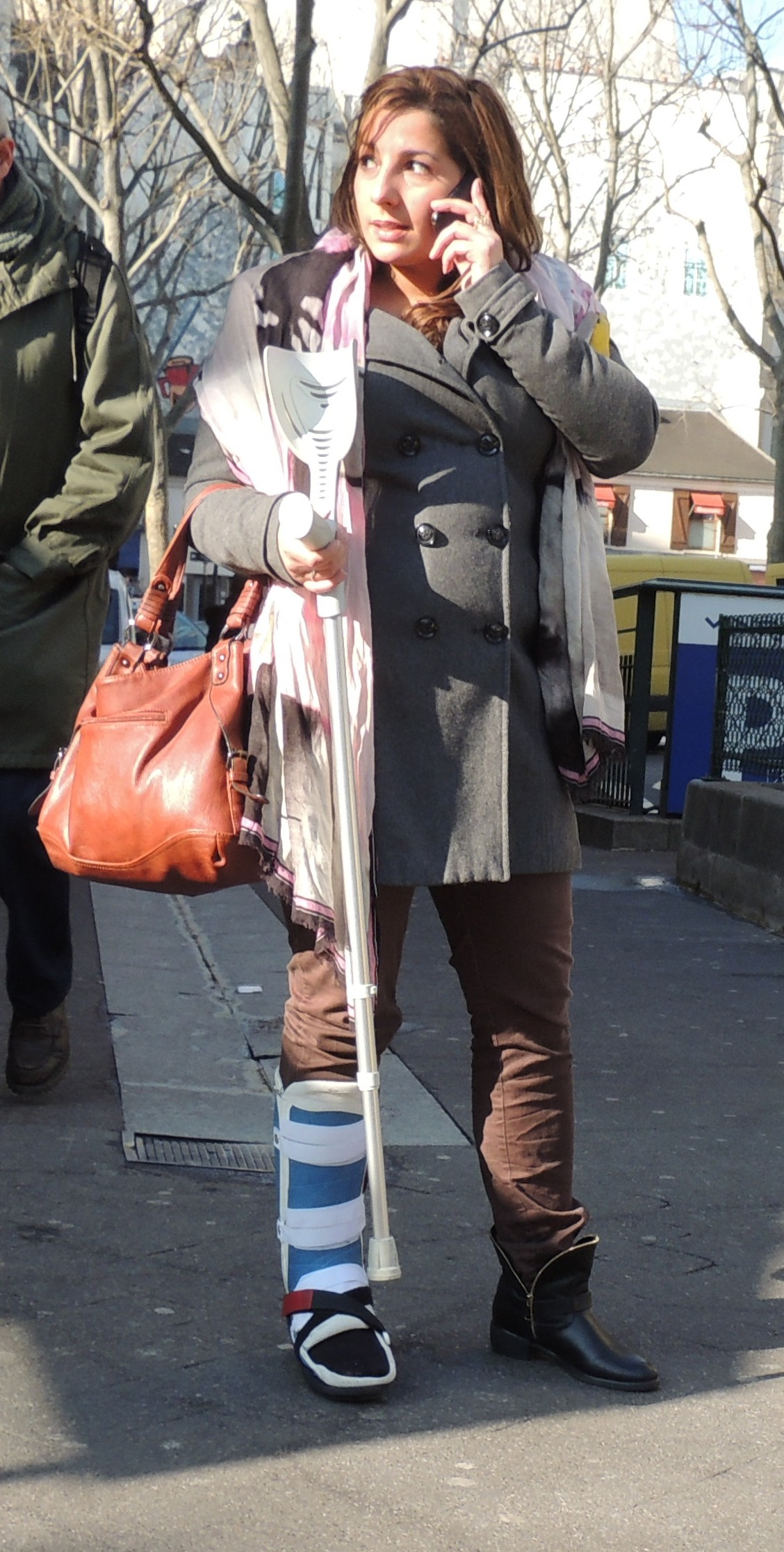 Woman in removable SLC on crutches.