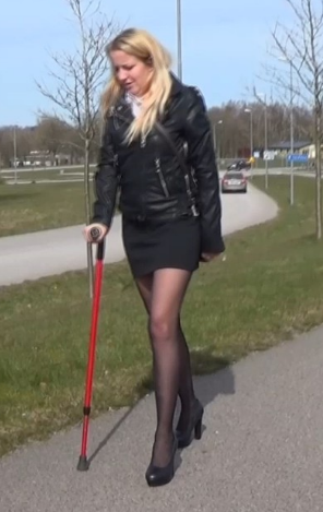 Alva Crutching #2004-4 - Alva limps across the parking lot and tries to catch the bus that will soon leave. With heels, and just a crutch, it is not easy to catch up on time. Alva tries to run, but with such a sore foot it does not work at all and...