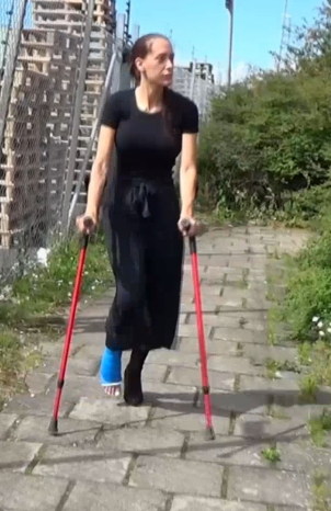 Sunshine LLC #63 - With a black top, black pants and a black heel boot on her left foot comes Sunshine crutching against us. She has a bent blue LLC on her right leg and she will now show us how good she is to go up and down stairs with her LLC.