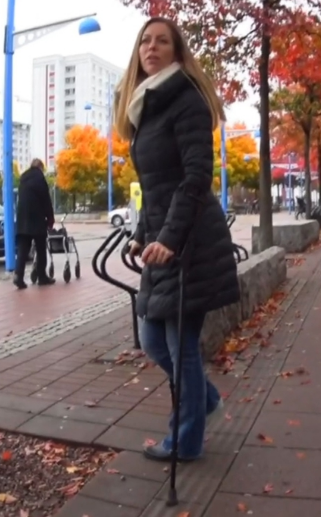 Melinda SLC #127 - Melinda crutches over a parking lot with long winter jacket, jeans and with gray sock over the casted right foot. She is on her way to a restaurant for a little lunch. Once again, she wants to show our photographer a bit of the...
