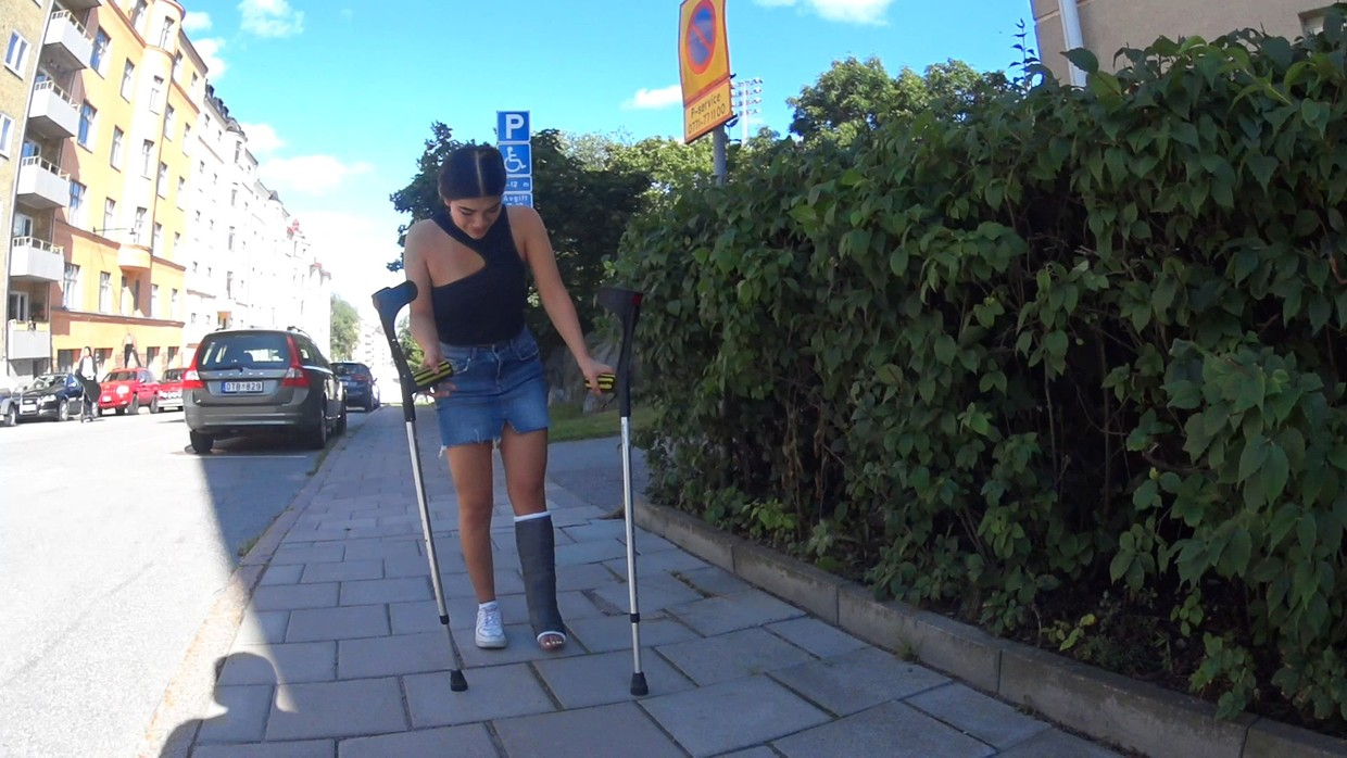 Pascale SLC - Can you see my cast and toes today? We meet Pascale when she comes crutching on a sidewalk up a hill. She is wearing a black top, blue denim skirt, a white sneaker on her right foot and a black cast on her left lower leg (Vid 17min $5)