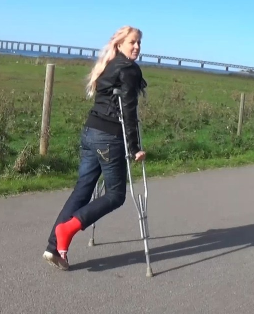 Alva SLC - Crutching at the seawalk a chance to look at the cast. She finds a place where she sits down to rest and removes her sock from her red SLC and rolls up her pants so you can see her cast. (Video: 12 min $7)