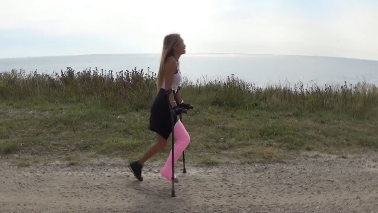 Bunny LLC - Bunny is out walking with a pink LLC on her right leg. Since she is crutching along the sea walk Bunny gets a nice view of the ocean. After a few minutes, Bunny gets up and enjoys the wind in her hair and the view of the sea...