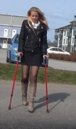 Alva on crutches - Alva limps forward with the help of her crutches. Wearing boots, skinny tights, a skirt and a leather jacket, Alva is on her way home from the office. Alva takes a shortcut across the lawn to visit the store before heading home.