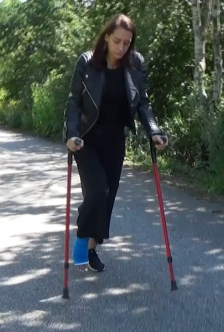Sunshine  LLC - With a blue LLC, dark clothes and a pair of sneakers, Sunshine is crutching up along the road. Her long hair flies with the wind where she, with the help of crutches, makes her way in the summer sun.