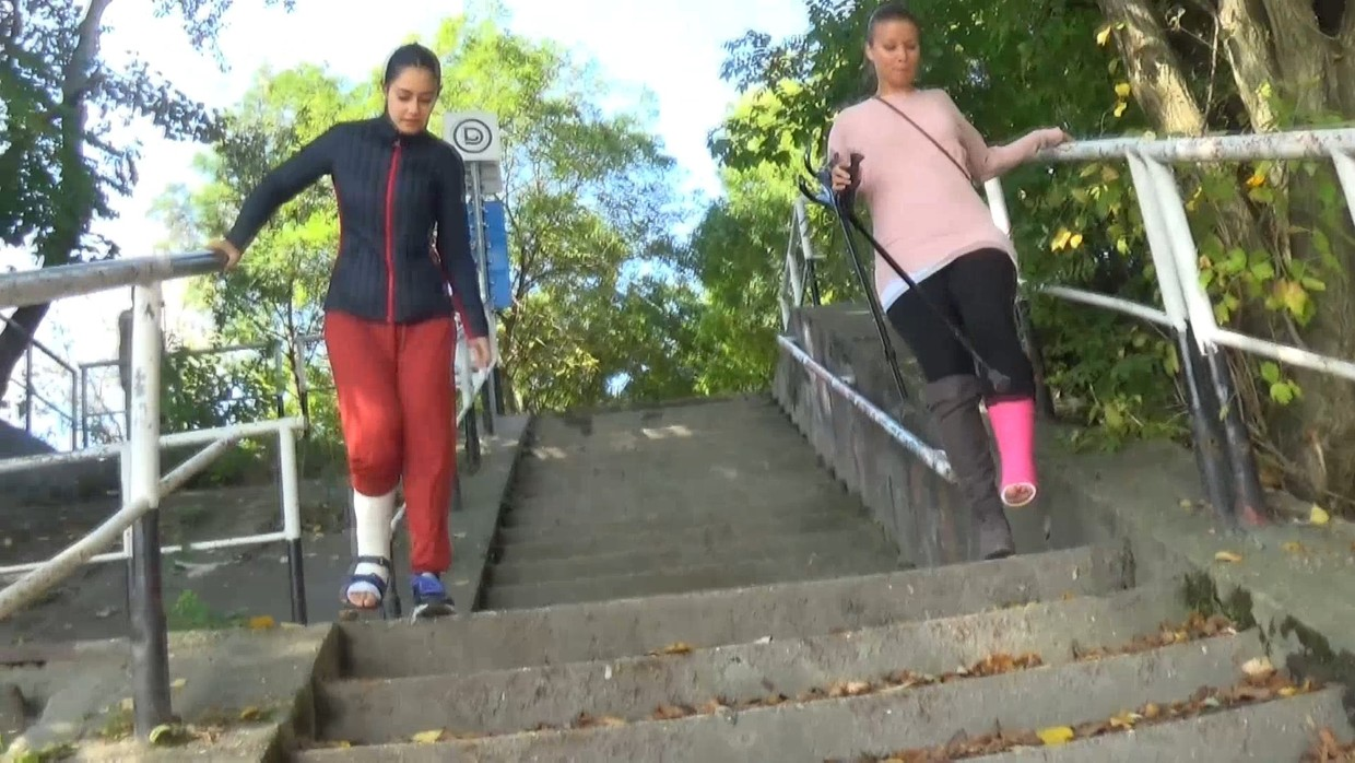 Lucy SLC & Elisabeth SLC - Lucy take her crutches and start crutching with her friend Elisabeth walking beside her. Elisabeth is also in a SLC but she has a cast shoe so she can walk on her cast. They come to some steps and both of them have to jump.