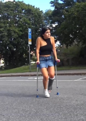 Pascale SLC - With a black SLC crutch Pascale along the streets of the city. She jumps with blue crutches and the warm weather allows for a skirt and a top and Pascale has chosen to wear white sneakers on her right foot.