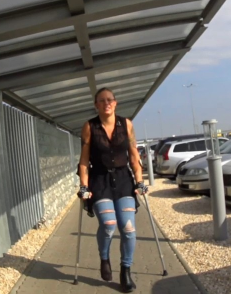 Sarah sprain on crutches - Sarah is traveling and has just picked up the luggage and is now on her way to the transport that will bring her and her friend to the hotel. Her right foot is bandaged and has only a thin nylon over which allows everyone..
