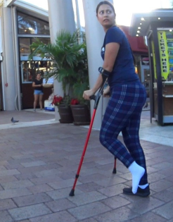 Elisabeth Sock Sprain -   Extra long clip. Elisabeth using her red crutches through a parking garage. Her left foot appears to be sprained so badly that she chose not to wear shoes on her foot. To get out of the parking garage, Elisabeth jumps down..