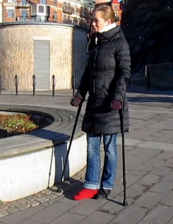Melinda SLC - Melinda has a red sock on her casted right foot. At a slow pace, Melinda jumps forward with the help of her crutches, through the city center where some people are out to shop as it is only a few weeks before Christmas.