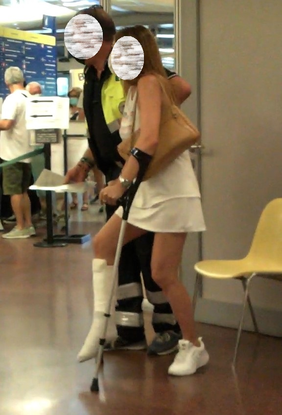 Blond woman in white SLC with crutches - This beautiful blonde woman broke her right ankle.  She is wearing a SLC with a blue sock on it.  The husband looks for a wheelchair but cannot find it.  Then she has to use crutches even if she is not very...